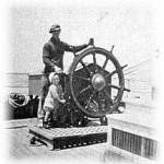 Capt Murchison & son at wheel (SK)